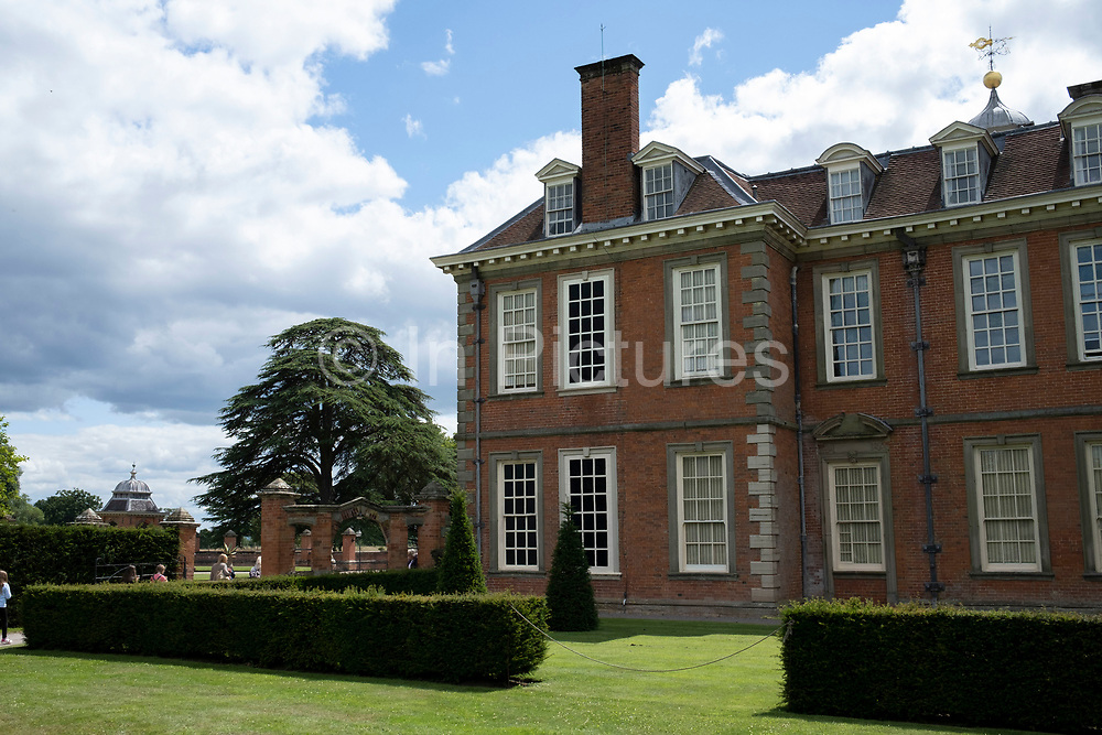 Blacked out windows are an excellent example of avoiding the window tax at Hanbury Hall on 10th July 2020 in Hanbury, United Kingdom. Window tax was a property tax based on the number of windows in a house. To avoid the tax some houses from the period can be seen to have bricked-up window-spaces ready to be glazed or reglazed at a later date. In England and Wales it was introduced in 1696 and was repealed 155 years later, in 1851. Hanbury Hall is a large 18th-century stately home standing in parkland at Hanbury, Worcestershire. The main range has two storeys and is built of red brick in the Queen Anne style. It is a Grade I listed building, and the associated Orangery and Long Gallery pavilion ranges are listed Grade II. It is managed by the National Trust and is open to the public.