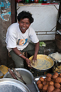 Street vendor sells Indian food off a street stall. Photographed in Cochin, India