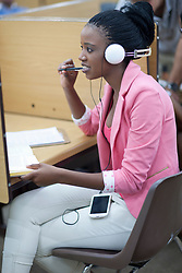 Female student working in library with headphones (Credit Image: © Image Source/Albert Van Rosendaa/Image Source/ZUMAPRESS.com)