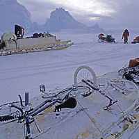 BAFFIN ISLAND, Nunavut, Canada. Mountaineering expedition & its Inuit guides' snowmobiles parked by iceberge on frozen Baffin Bay.