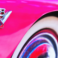Wheel and V8 detail of hot pink Ford Crown Victoria classic car.