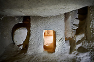 Pictures & images of cave room with a defensive entrance , Aynali Kilise cave church, 11th century, near Goreme, Cappadocia, Nevsehir, Turkey<br /> <br /> It can be seen that the inner room is enterd via a very small tunnel. The tunnel has a groove cut into it and the round rock rolls into this sealing the tunnel and stopping any attackers from entering the inner room. Stairs can be seen to the right of the door leading up to the upper gallery rooms of the monastery. .<br /> <br /> If you prefer to buy from our ALAMY PHOTO LIBRARY  Collection visit : https://www.alamy.com/portfolio/paul-williams-funkystock/cappadociaturkey.html (TIP refine search - type which part of Cappadocia into the LOWER search box)<br /> <br /> Visit our TURKEY PHOTO COLLECTIONS for more photos to download or buy as wall art prints https://funkystock.photoshelter.com/gallery-collection/3f-Pictures-of-Turkey-Turkey-Photos-Images-Fotos/C0000U.hJWkZxAbg