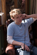 ICE.MWdrv04.06.xrw..Gunnlaugur Bjornsson, 23, on the phone while visiting his parents. {{He has a girlfriend and a baby.}}.Ten years ago he and his family, the Thoroddsen's, were the Icelandic participants in Material World: A Global Family Portrait, 1994 for which they took all of their possessions out of their house for a family and possessions portrait in the snow. Pages 162-163. Phone, Mobile, Telephone. {{Central image from original book project is: ICE.mw.01.xxs.}}.