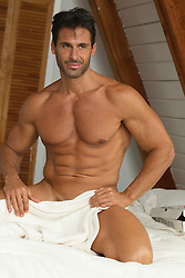 nude muscular man at home in bed