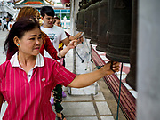 29 MAY 2018 - BANGKOK, THAILAND: Women ring prayer bells to make merit during Vesak observances at Wat Hua Lamphong in Bangkok. Vesak is the Buddha's birthday, and one of the most important holy days in the Theravada Buddhist religion. Many Thais visit their local temples for Vesak and rededicate themselves to the Dharma, listen to talks about Buddhism and make merit by bringing flowers to the temple.        PHOTO BY JACK KURTZ