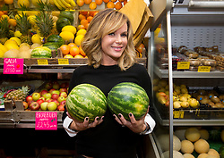 Amanda Holden autobiography signing.<br /> Amanda Holden holding a couple of melons before signing her autobiography at the village grocers 'Hylands' where she once worked in her hometown of Bishops Waltham, United Kingdom, Wednesday, 6th November 2013. Picture by i-Images