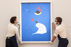 © Licensed to London News Pictures. 23/07/2020. London, UK.  Sotheby's staff member hang a painting titled Peinture (Femme au chapeau rouge) (1927) by artist Joan Miro with an estimate of £20-30 million. Works spanning over half a millennium of art history go on display at Sotheby's London ahead of a one-off auction on July 28. Titled 'Rembrandt to Richter', the sale will offer the very best from Old Masters, Impressionist & Modern Art, Modern & Post-War British Art and Contemporary Art – travelling from the Italian Renaissance through to Pop Art. Photo embargoed for usage until 24th July 2020 09:00. Photo credit: Ray Tang/LNP