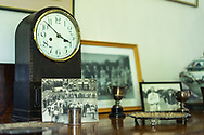 House room interior with old furniture including picture frame of golfers from the 1930s and a small comemorative golf cup