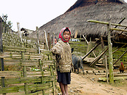 A young girl wearing a headskarf in the remote Akha Nuquie village of Ban Peryenxangmai, Phongsaly province, Lao PDR. Whilst there is a small primary school in Ban Peryenxangmai not all children are able to attend as their parents cannot afford the fees and need them to work at home or take care of younger siblings.
