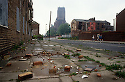 A low, wide landscape of dereliction and poverty during the early 1990s in the city of Liverpool, England. The Catholic cathedral rises high in the distance over near-empty streets where bricks and refuse litter the pavements and empty buildings await destruction - the impoverished population having moved out for a better life elsewhere.