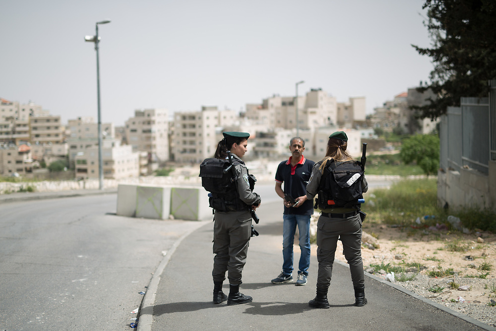 Israeli Border Police Women Staff Sergeant Chen Cohen (R) and Corporal Mor Hadad (L) inspect a Palestinian pedestrian at the exit of the East Jerusalem neighborhood of Issawiya, in Jerusalem, Israel, on April 10, 2016.