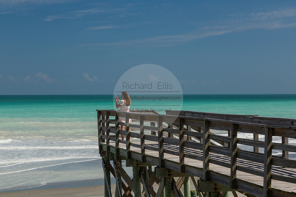A young woman takes a camera phone photo of the clear turquoise water from a  walkway to the beach at Folly Beach, SC.