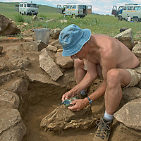 """Smithsonian archaeologist Dr. William Fitzhugh take compass bearing on the orientation of an ancient horse skull in a 2700+ year-old, bronze age  """"khirigsuur"""" burial mound at Ulaan Tolgoi site near Lake Erkhel, north of Muren, Mongolia."""