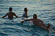 Female Surfer and couple wading in the water at Waikiki Beach, Honolulu, Oahu, Hawaii