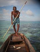 Old man named Sahad fishing with net and pole off Bodgaya island.