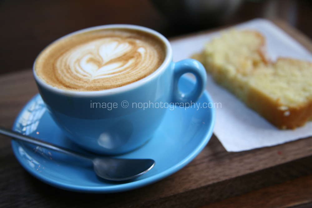 Close up of a cup of cappuccino coffee in a blue cup and saucer with lemon drizzle cake
