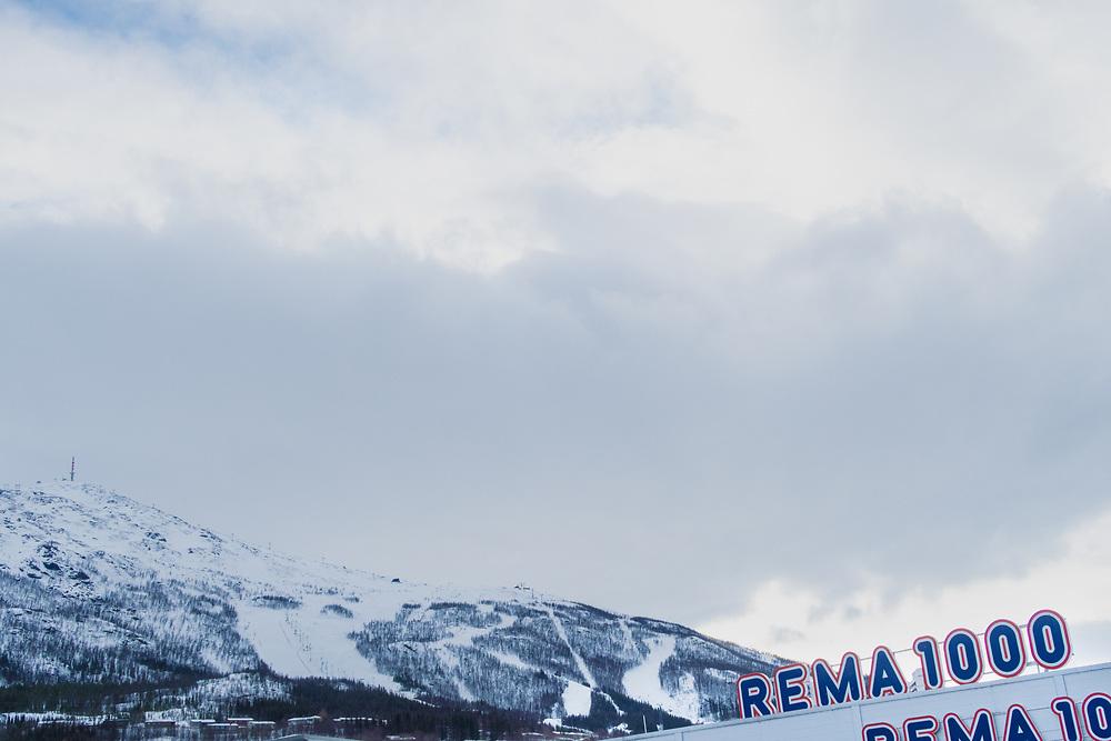 Rema 1000 i Rombaksveien i Narvik. Foto med tekstområde i skyene.