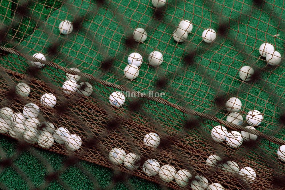 view through a net of a pile of golf balls
