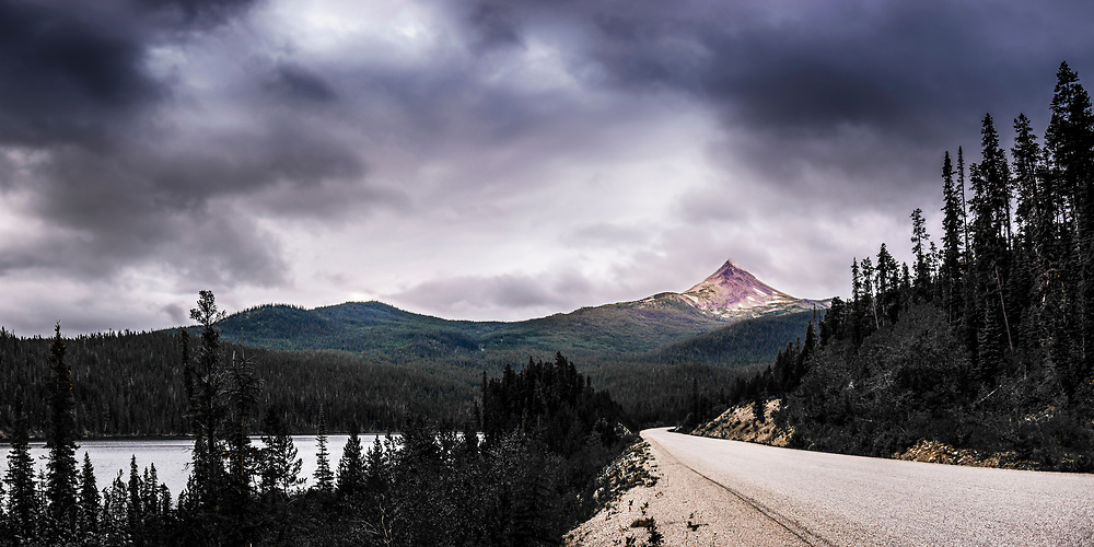 Panorama of Pyramid Mountain in summer with Cotton Lake on the left and the Dease Lake Highway on the right