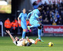 Swansea City's Jordi Amat tackles Tottenham Hotspur's Emmanuel Adebayor - Photo mandatory by-line: Joe Meredith/JMP - Tel: Mobile: 07966 386802 19/01/2014 - SPORT - FOOTBALL - Liberty Stadium - Swansea - Swansea City v Tottenham Hotspur - Barclays Premier League