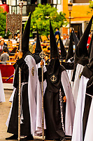 Hooded Penitents (Nazarenos) in the procession of the Brotherhood (Hermandad) La Sed, Holy Week (Semana Santa), Seville, Andalusia, Spain.