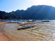 Moored pump boats along shore with mountains rising up in background, El Nido, Palawan, Philippines, Southeast Asia