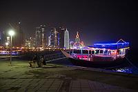 """08 APR 2013, DOHA/QATAR<br /> Im Hintergrund Downtown Doha mit den Hochhaeusern Palm Towers (2. u. 4. v. links), Tornado Tower (3. v.L.) Al Bidda Tower (5. v.L.), Qatar World Trade Center (Qatar General Insurance Reinsurance Company) (2.v.R.), und Doha Tower, auch """"Condom Tower"""" (rechts), vorne eine beleuchtete Dau oder Dhau, ein Schiff das fuer Ausfahrten gemietet werden kann, gesehen von der Al Corniche Street<br /> IMAGE: 20130408-01-047<br /> KEYWORDS: Katar, Hochaus, Wolkenkratzer, Tower, Skyscraper, Nacht, Nachtaufnahme, night"""