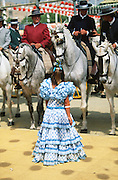 """Riders, men and women dress up in their finery, the traditional """"traje corto"""" (short jacket, tight trousers and boots) for men and the """"faralaes"""" or """"trajes de flamenca"""" (flamenco style dress) for women. The men traditionally wear hats called """"cordobés""""...The Feria de abril de Sevilla, """"Seville April Fair"""" dates back to 1847. During the 1920s, the feria reached its peak and became the spectacle that it is today. It is held in the Andalusian capital of Seville in Spain. The fair generally begins two weeks after the Semana Santa, Easter Holy Week. The fair officially begins at midnight on Monday, and runs six days, ending on the following Sunday. Each day the fiesta begins with the parade of carriages and riders, at midday, carrying Seville's citizens to the bullring, La Real Maestranza...For the duration of the fair, the fairgrounds and a vast area on the far bank of the Guadalquivir River are covered in rows of casetas (individual decorated marquee tents which are temporarily built on the fairground). Some of these casetas belong to the prominent families of Seville, some to groups of friends, clubs, trade associations or political parties. From around nine at night until six or seven the following morning, at first in the streets and later only within each caseta, crowds of people party and dance Sevillanas, traditional Flamenco dances, Sevillan style drinking Jerez sherry, or Manzanilla wine, and eating tapas."""