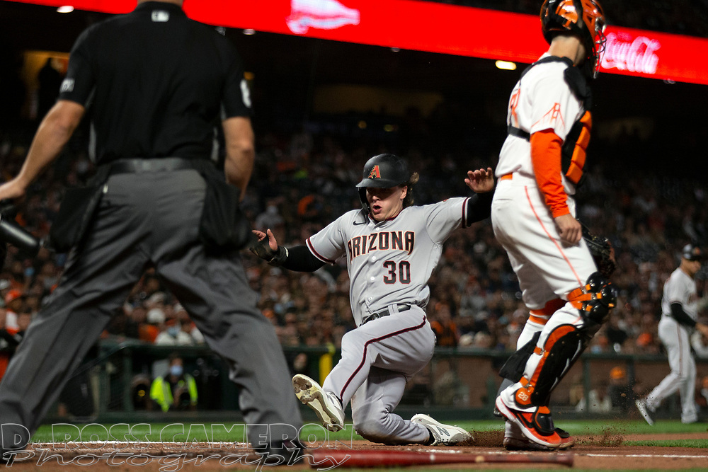 Arizona Diamondbacks' Jake McCarthy (30) slides home safely on Josh Rojas's sacrifice fly to left field as San Francisco Giants catcher Buster Posey (28) waits for the relay. during the third inning of a baseball game, Tuesday, Sept. 28, 2021, in San Francisco. Umpire is Scott Barry. (AP Photo/D. Ross Cameron)
