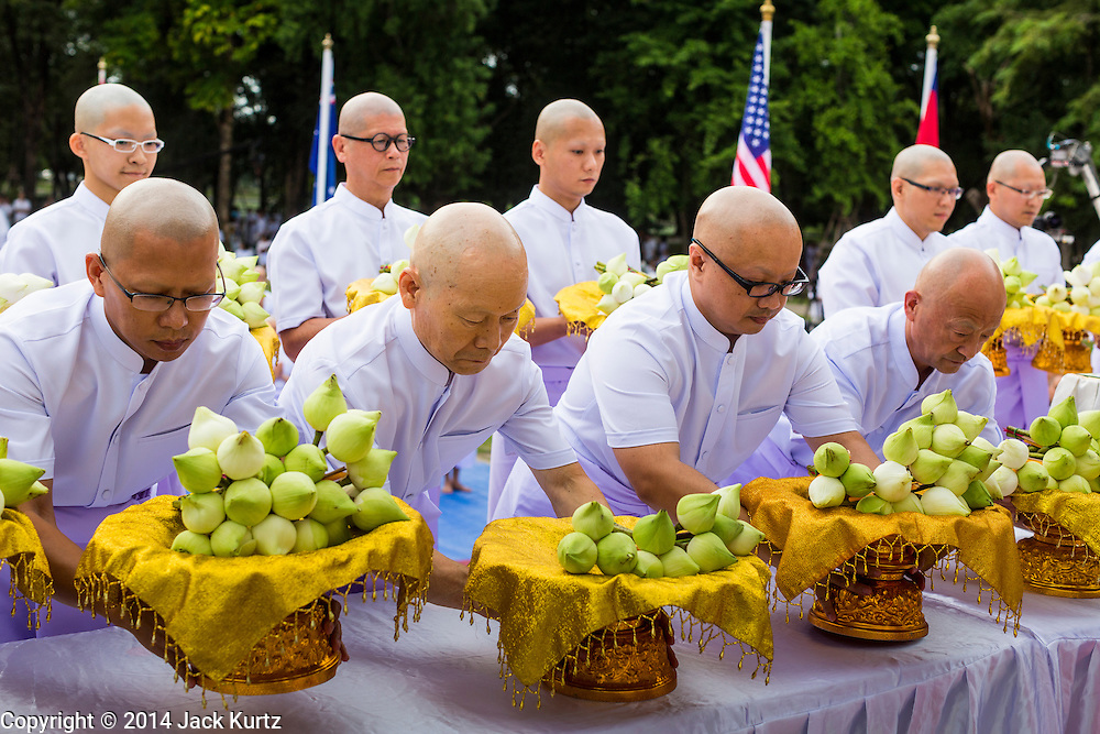 19 JULY 2014 - KHLONG LUANG, PATHUM THANI, THAILAND: Men who will be ordained as Buddhist monks present lotus blossoms and pray in front of the ordination hall at Wat Phra Dhammakaya. Seventy-seven men from 18 countries were ordained as Buddhist monks and novices at Wat Phra Dhammakaya, a Buddhist temple  north of Bangkok, Saturday. It is the center of the Dhammakaya Movement, a Buddhist sect founded in the 1970s and led by Phra Dhammachayo (Phrathepyanmahamuni). It is the largest temple in Thailand. The Dhammakaya sect has an active outreach program that attracts visitors from around the world.    PHOTO BY JACK KURTZ