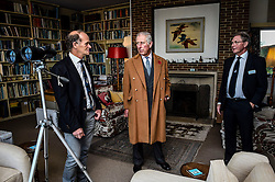 The Prince of Wales speaks with Falcon Scott (left), grandson of explorer Robert Falcon Scott, and WWT Chief Executive CBE Martin Spray (right), as they take a tour around his father Sir Peter Scott's house, during a visit to the Wildfowl and Wetlands Trust's Slimbridge Wetland Centre in Gloucestershire to celebrate its 70th anniversary.