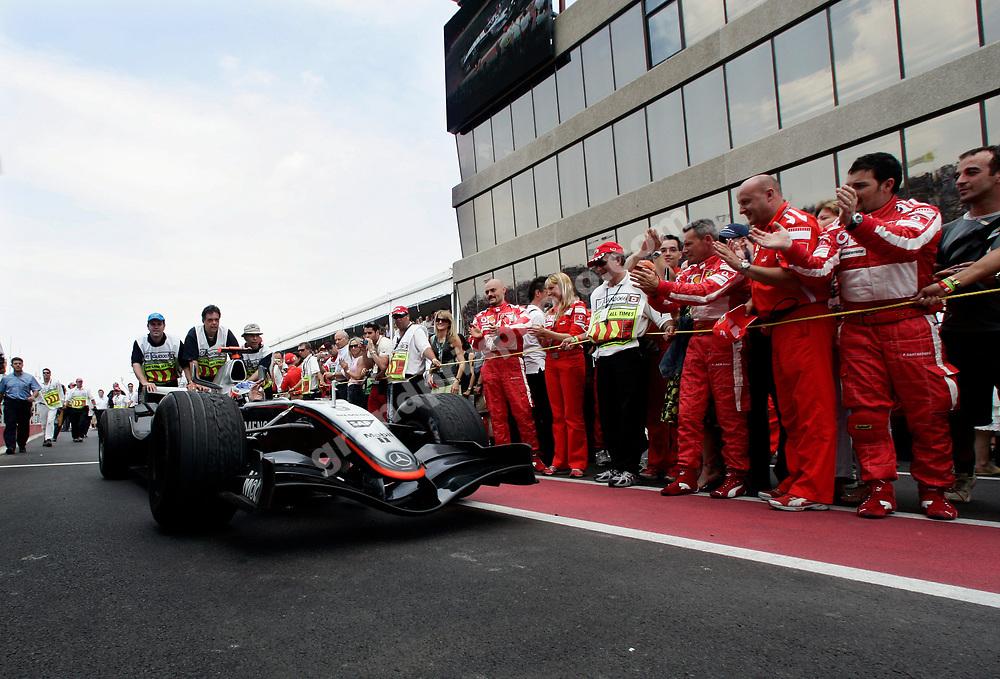 Ferrari mechanic applaud race winner Kimi Raikkonen (McLaren-Mercedes) after the 2005 Canadian Grand Prix at the Circuit Gilles Villeneuve in Montreal. Photo: Grand Prix Photo