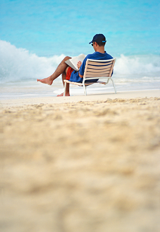 Man sitting in beach chair and reading with ocean surf