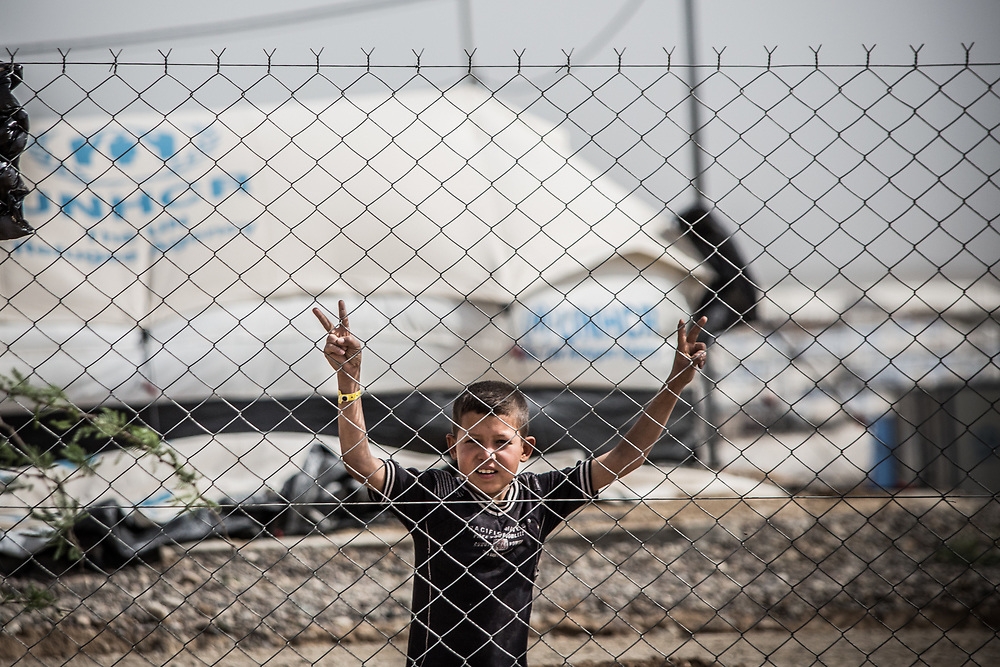 A boy in a refugee camp poses for a picture near West Mosul.