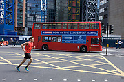 A mid-afternoon jogger runs over the junction of Bishopsgate as a London double-decker bus advertising Sky Sports drives south. With a theme of sporting endeavour and personal fitness alongside the corporate message of this broadcaster, advertising its brand on London's public transport. Striding across the box junction on this ancient thoroughfare in the City of London, the capital's financial heart, the man heads south while listening to mp3 music on a personal device.