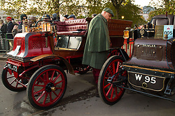 EDITORIAL USE ONLY A man in period dress views vehicles lined up before the start of the Bonhams London to Brighton Veteran Car Run at Hyde Park Corner in London.