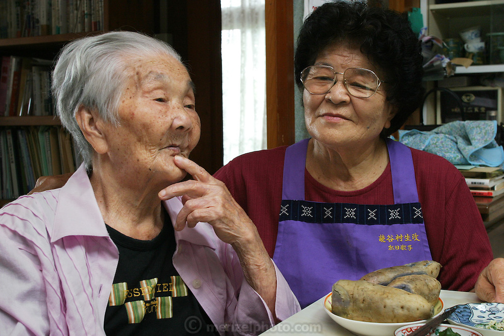 """(MODEL RELEASED IMAGE). Tama Matsuda, 100 years old, and her daughter-in-law Keiko, 75, with beni imo -purple Okinawan potatoes that they are eating for lunch. (Supporting image from the project Hungry Planet: What the World Eats) The Matsuda family is one of the thirty families featured in the book Hungry Planet: What the World Eats (p. 186). Hara hachi bu: """"eat only until 80 percent full,"""" say older Okinawans. The island has been the focus in recent years of researchers trying to discover why a disproportionately large number of Okinawans are living to age 100 or more."""