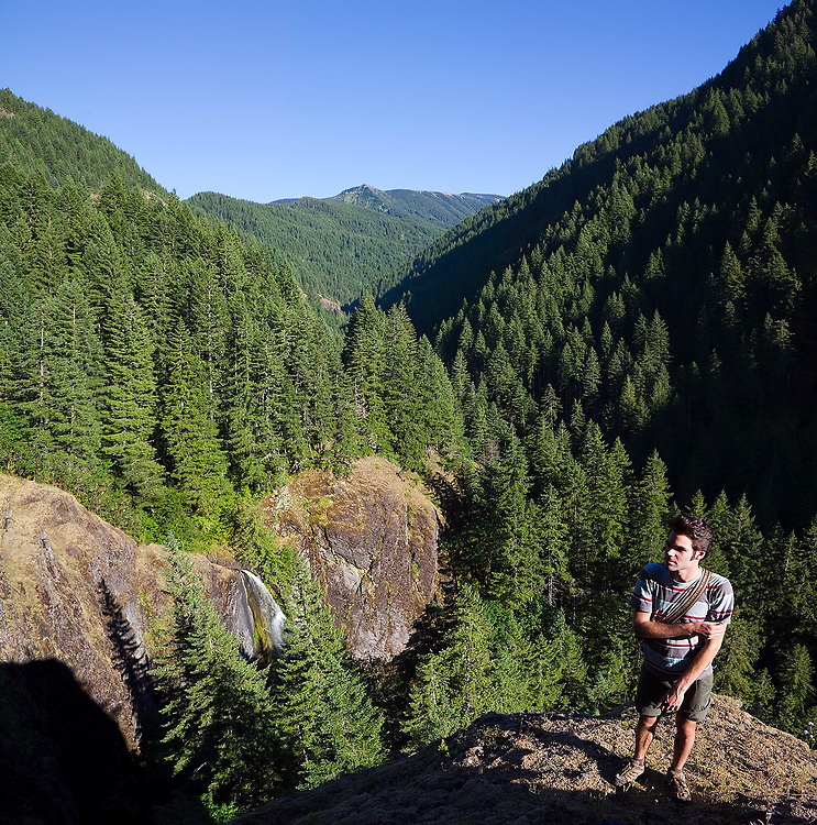 Hiker Hamilton Boyce enjoys the view of a waterfall and the lush Eagle Creek valley from the Eagle-Benson Trail, Columbia River Gorge National Scenic Area, Oregon.