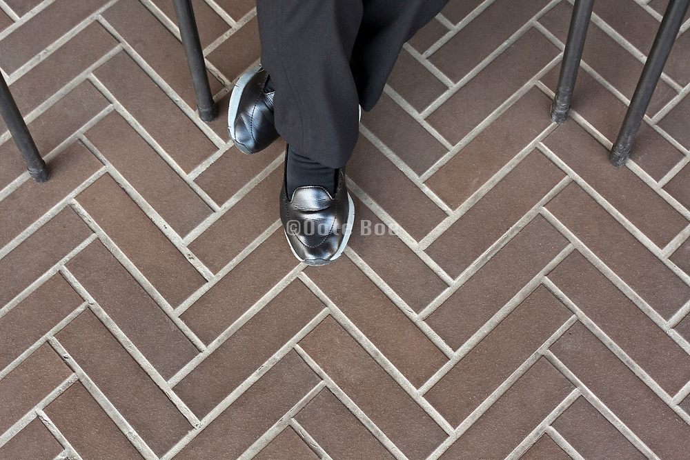 person sitting wearing shiny black shoes