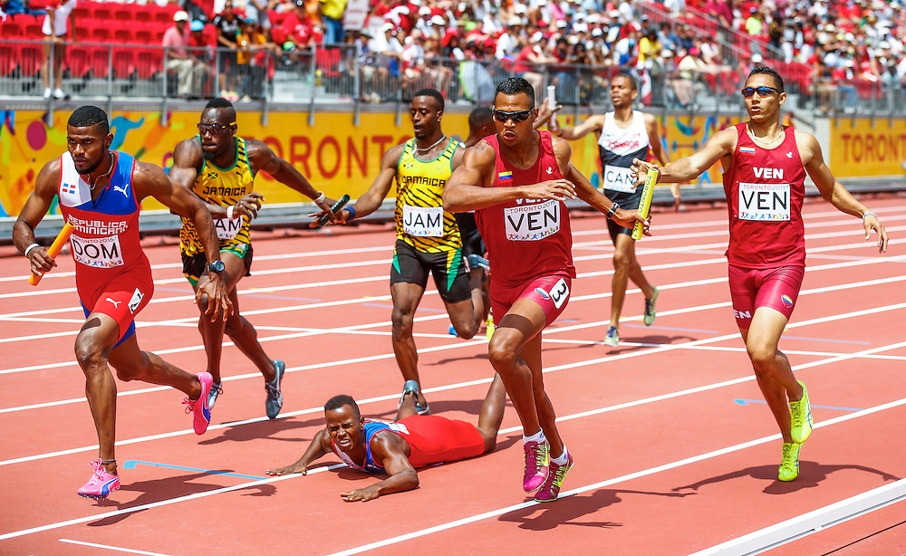 Joel Mejia of the Dominican Republic falls in the men's 4x400m relay during the athletics at the Pan Am Games in Toronto, Friday July 24, 2015.    THE CANADIAN PRESS/Mark Blinch