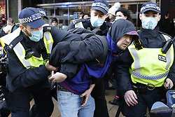 © Licensed to London News Pictures. 19/12/2020. London, UK. Police arrest an anti-lockdown protester as they march along Oxford Street in central London. Hundreds of police, some in riot gear, have started to arrest demonstrators. Photo credit: Peter Macdiarmid/LNP