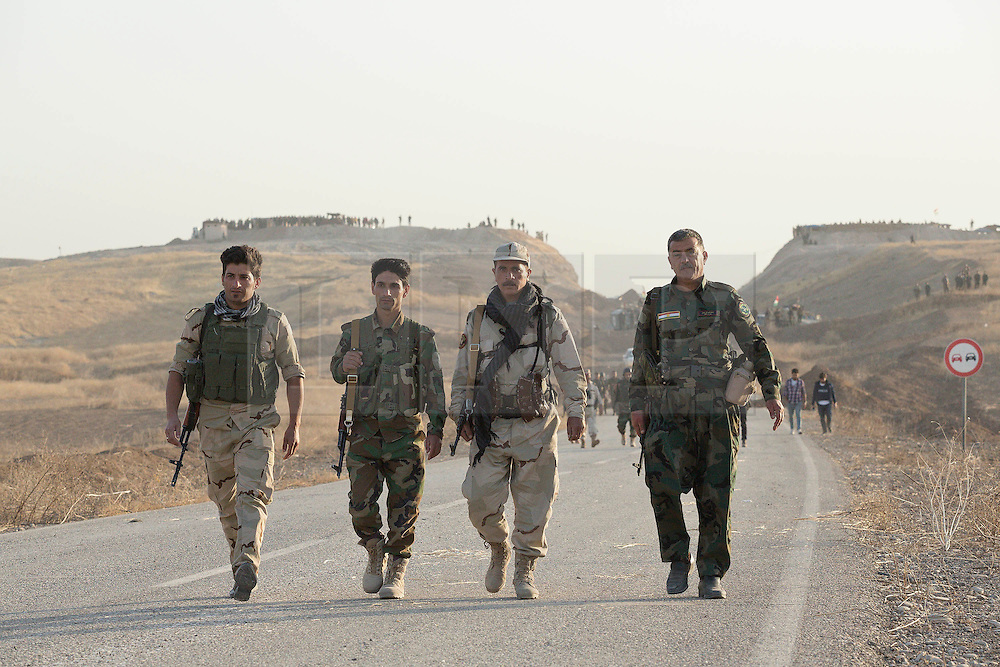 20/10/2016. Bashiqa, Iraq. Four Kurdish peshmerga fighters advance along a road at the beginning of a large offensive to retake the Bashiqa area, and eventually Mosul, from Islamic State militants today (20/10/2016).<br /> <br /> Launched in the early hours of today with support from coalition special forces and air strikes, the attack is part of the larger operation to retake Mosul from the Islamic State, and involves both the Kurds and the Iraqi Army. The city of Bashiqa, around 9 miles north of Mosul, is one of several gateway areas that must be taken before any attempted offensive on Mosul itself.<br /> <br /> Despite the peshmerga suffering several casualties after militants fought back using mortars, heavy machine guns and snipers, the Kurdish forces were quickly taking ground with Haider al-Abadi, the Iraqi prime minister, stating that the operation to retake Mosul was progressing faster than expected. Photo credit: Matt Cetti-Roberts/LNP