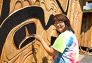 Woman native artists works on her totem pole carvings Potlatch Park, Ketchikan, Alaska