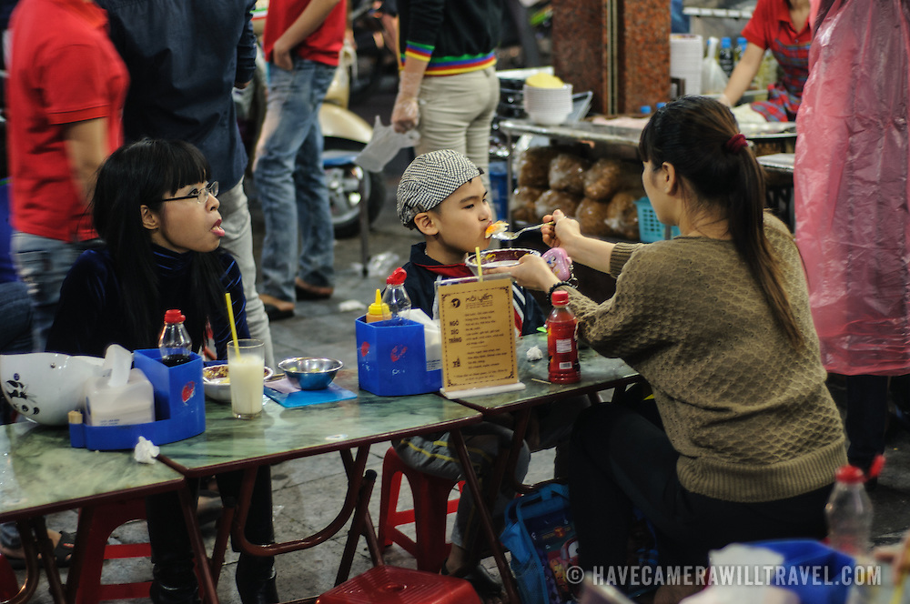 A mother feeds her young son at a streetside food vendor in Hanoi's Old Quarter.