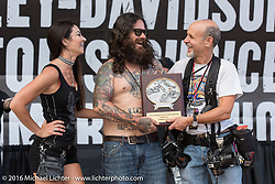 Custom motorcycle builder Noah O'Geen receiving the Lowride Magazine Italy award from Michael Lichter at the Harley-Davidson Editors Choice Custom Bike Show on the HD Rallypoint stage on Main Street during the annual Sturgis Black Hills Motorcycle Rally.  SD, USA.  August 9, 2016.  Photography ©2016 Michael Lichter.