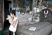 A mother kissing her newborn daughter at the house where she lives in the cemetery.