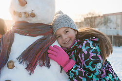 Portrait of girl leaning on snowman