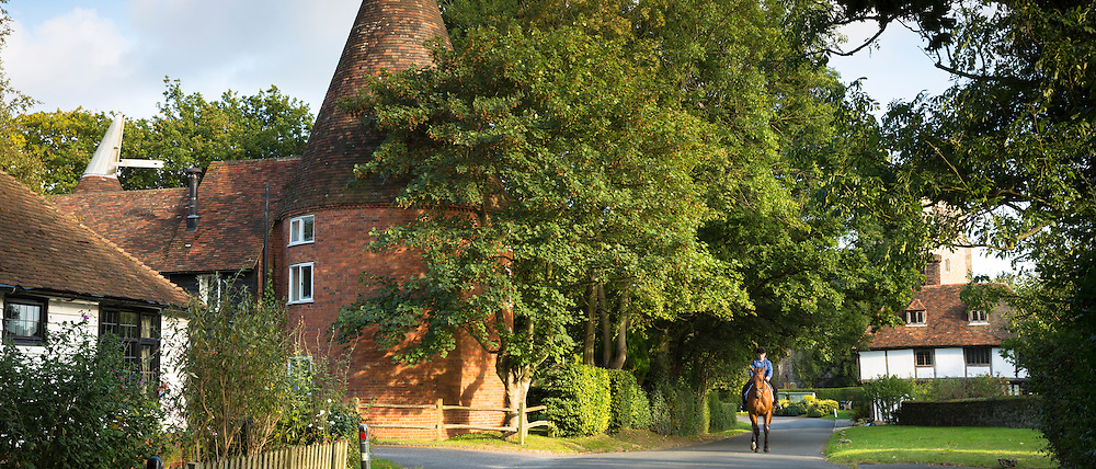 Horse and rider in quaint attractive village of Smarden with traditional Kentish oast house in High Weald in Kent, England, UK