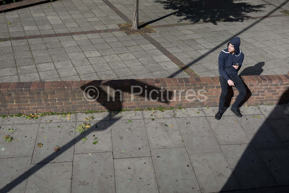 Aerial view of a youth using a mobile phone on next a diagonal pavement line, 21st September 2018, in London England.