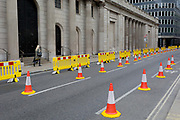 As the UKs Conornavirus pandemic lockdown continues, but with travel restrictions and social distancing rules starting to ease after three months of closures and isolation, Londoners pass yellow barriers and social distance cones which have narrowed the road in favour of wider pedestrian pavements outside the Bank of England on Threadneedle Street, on 9th June 2020, in London, England.